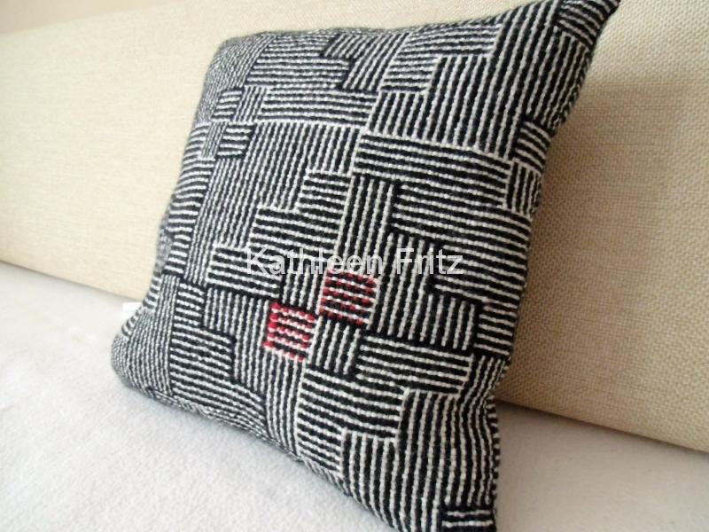 Kissen in schwarz- weiß mit einem Klecks rot